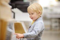 Famiglia con il ragazzino che sceglie la mobilia giusta per il loro appartamento in un negozio di mobili domestico moderno Fotografia Stock
