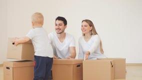 Famiglia con il ragazzo che disimballa le scatole di cartone commoventi a nuova casa stock footage