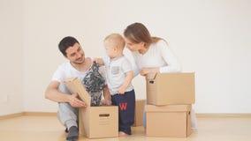 Famiglia con il ragazzo che disimballa le scatole di cartone commoventi a nuova casa video d archivio