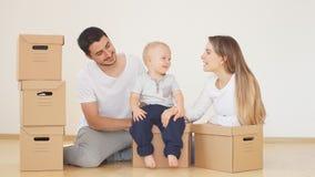 Famiglia con il ragazzo che disimballa le scatole di cartone commoventi a nuova casa archivi video