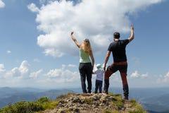 Famiglia con la bambina che celebra l'aumento sopra la montagna Concetto di Parenting immagini stock