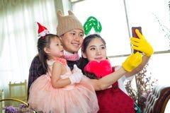 Famiglia con la bambina in giardino che prende selfie dal telefono cellulare Immagini Stock