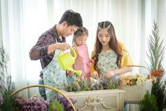 Famiglia con la bambina nel giardinaggio del gioco Immagini Stock