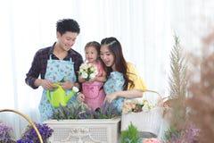 Famiglia con la bambina nel giardinaggio del gioco Fotografia Stock