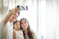 Famiglia con la bambina in parco che prende selfie dal telefono cellulare Fotografia Stock