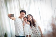 Famiglia con la bambina in parco che prende selfie dal telefono cellulare Fotografia Stock Libera da Diritti