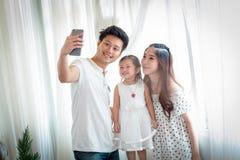 Famiglia con la bambina in parco che prende selfie dal telefono cellulare Immagini Stock Libere da Diritti