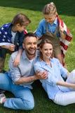 Famiglia con la bandiera americana che abbraccia all'aperto, concetto di festa dell'indipendenza Fotografia Stock Libera da Diritti