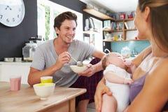 Famiglia con la figlia del neonato alla Tabella di prima colazione Immagini Stock Libere da Diritti