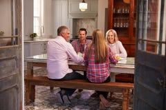 Famiglia con la prole adulta che gode del pasto a casa insieme immagine stock