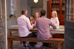 Famiglia con la prole adulta che gode del pasto a casa insieme immagini stock