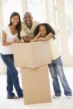 Famiglia con le caselle nel nuovo sorridere domestico Immagini Stock Libere da Diritti