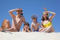 Famiglia con le mascherine naviganti usando una presa d'aria che si siedono sul sa Fotografia Stock Libera da Diritti