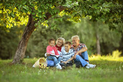 Famiglia con le mele e libro in parco Fotografia Stock
