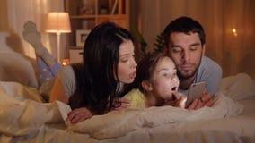 Famiglia con lo smartphone a letto alla notte a casa video d archivio