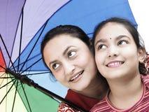 Famiglia con un ombrello grazioso Immagine Stock
