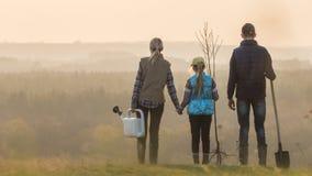 Famiglia con una piantina dell'albero, uno spruzzatore e una condizione della pala in un posto pittoresco immagine stock