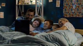 Famiglia contenta che guarda film divertente sul computer portatile immagini stock