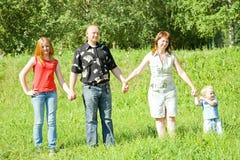 Famiglia da quattro basamenti su erba fotografie stock libere da diritti