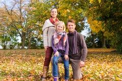 Famiglia davanti agli alberi variopinti in autunno o in caduta Fotografie Stock