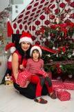 Famiglia davanti all'albero di Natale Fotografie Stock Libere da Diritti