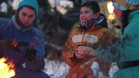 Famiglia dei giovani della foresta di inverno che si siede nel legno dal fuoco, bevande calde beventi dai termos e friggente le s video d archivio