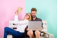 Famiglia dei nerd Coppia i nerd che studiano il lavoro con il libro ed il computer portatile La famiglia in occhiali passa tutto  immagine stock libera da diritti