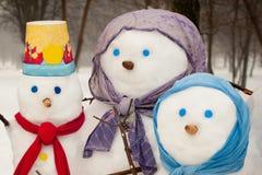 Famiglia dei pupazzi di neve all'aperto Fotografia Stock