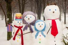 Famiglia dei pupazzi di neve all'aperto Immagine Stock Libera da Diritti