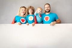 Famiglia dei supereroi che giocano a casa immagini stock