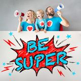 Famiglia dei supereroi che tengono insegna immagine stock libera da diritti