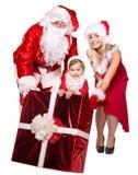 Famiglia del Babbo Natale con il contenitore di regalo della tenuta del bambino. Immagine Stock