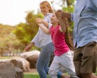 Famiglia del padre della figlia e della madre che gioca e che cammina intorno al parco immagini stock libere da diritti