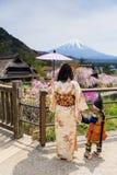 Famiglia del vestito dal giapponese con Sakura ed il mt fuji Immagini Stock