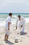 Famiglia dell'afroamericano che gioca gioco del calcio sulla spiaggia Fotografia Stock Libera da Diritti