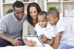 Famiglia dell'afroamericano che per mezzo del calcolatore del ridurre in pani fotografia stock