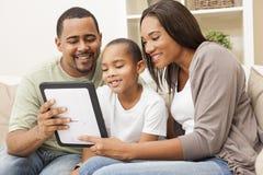 Famiglia dell'afroamericano che per mezzo del calcolatore del ridurre in pani Fotografie Stock Libere da Diritti