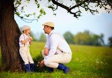 Famiglia dell'agricoltore divertendosi sotto un vecchio albero, campagna della molla Immagini Stock Libere da Diritti