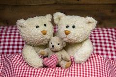 Famiglia dell'orsacchiotto con un bambino che si trova in un letto a quadretti rosso Fotografie Stock Libere da Diritti