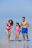 Famiglia della madre, del padre & della figlia che funziona sulla spiaggia Immagini Stock Libere da Diritti