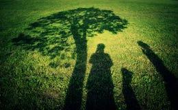 Famiglia della siluetta nel campo di erba Immagine Stock Libera da Diritti