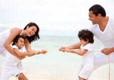 Famiglia della spiaggia che tira una corda Immagine Stock