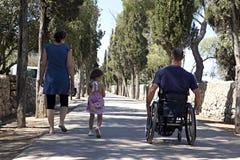 Famiglia della strada della sedia a rotelle Fotografie Stock