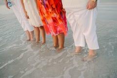 Famiglia delle donne che stanno che affronta l'oceano in acqua bassa Shoreline alla spiaggia sull'esterno di vacanza in natura fotografia stock libera da diritti