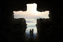 Famiglia dentro la caverna con un simbolo trasversale Fotografia Stock