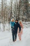 Famiglia di camminata con un bambino La famiglia cammina in natura nell'inverno Passeggiata della famiglia di inverno in natura M fotografia stock libera da diritti