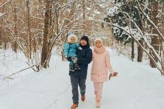 Famiglia di camminata con un bambino La famiglia cammina in natura nell'inverno Passeggiata della famiglia di inverno in natura M fotografia stock
