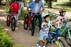 Famiglia di diverse generazioni che cammina con la bicicletta in parco fotografia stock