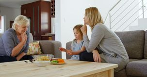 Famiglia di diverse generazioni che gioca gioco da tavolo in salone 4k video d archivio