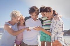 Famiglia di diverse generazioni facendo uso del telefono cellulare alla spiaggia Immagine Stock Libera da Diritti